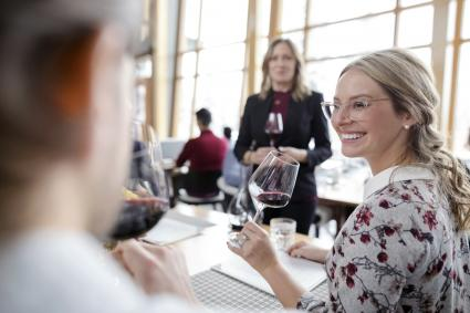 Mujer sonriente cata de vino tinto