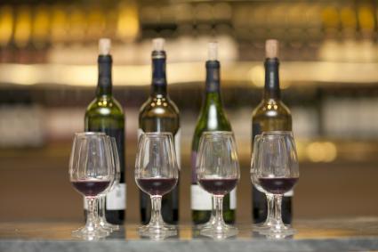 Copas de vino tinto y botellas de vino en un mostrador de una bodega