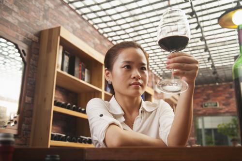 Mujer mirando una copa de vino tinto