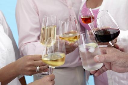 Personas levantando copas de vino en un brindis