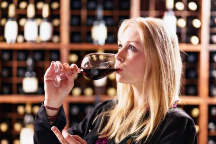 Mujer bebiendo vino tinto en el centro de degustación de bodegas