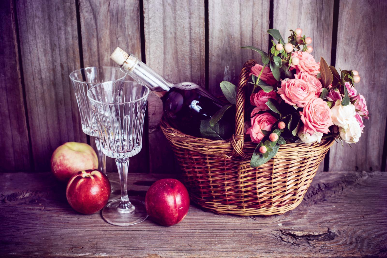 cesta de mimbre y una botella de vino rosado con dos copas y nectarinas