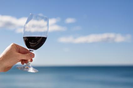 Mano sosteniendo una copa de vino tinto.