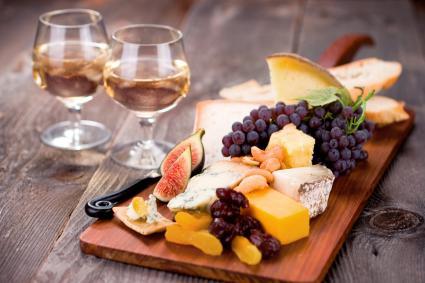 Tabla de quesos rellena con una variedad de quesos y servida con vino de postre