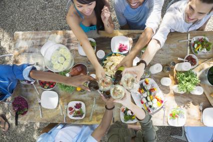 Amigos brindando copas de vino mesa de patio