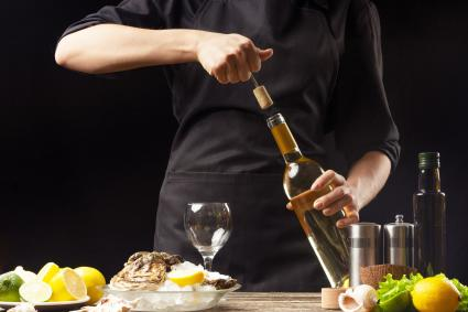Chef abre vino seco italiano con ostras con limón