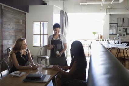 Camarera sirviendo vino a las mujeres en el café