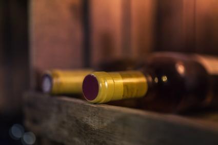 Dos botellas de vino tinto en estante de madera