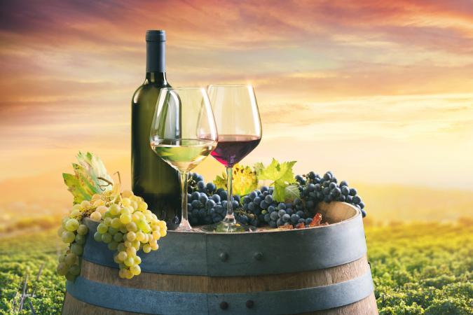 Botella y copas de vino en barril en viñedo al atardecer