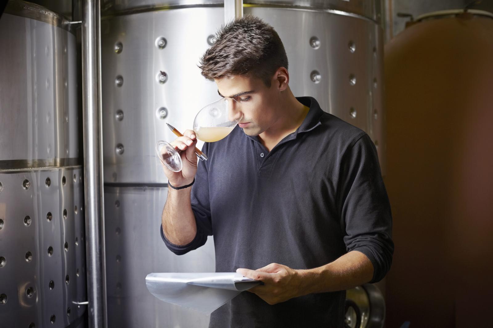 Experto en vinos oliendo muestra de vino blanco