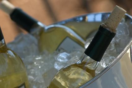 Botellas de vino blanco enfriándose en una tina de hielo