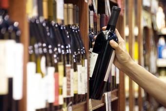 La mano de una mujer se extiende para seleccionar una botella de vino tinto.