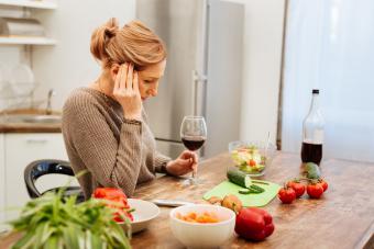 Mujer en la cocina con comida y vino